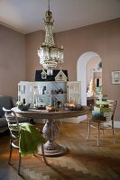 English dolls' house on round wooden table below chandelier in traditional dining room with modern ambiance