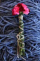 Tied bunch of pinks on pile of blue felt cords