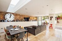 Open-plan interior in modern extension with exposed brickwork, designer furniture and access to terrace