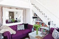 White-framed mirror above purple sofa set in front of open staircase in living room; bookcase in niche below stairs