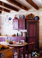 French country-house kitchen with aubergine cupboards and rustic dining area in farmhouse
