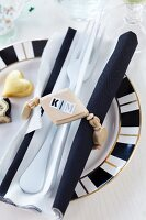 Wooden bead napkin ring with name on stickers around cutlery and black and white linen napkin on patterned plate