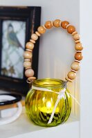 Yellow glass tealight holder with wooden beads threaded on wire handle