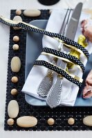 Cutlery and napkin tied with black and gold ribbon on place mat with wooden beads
