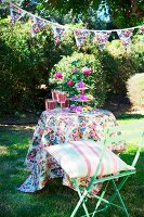 Festively decorated garden with bunting above table, floral tablecloth, cake stand of pastries and drinks; striped cushion on pastel green folding chair in foreground