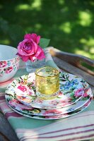 Stacked floral plates on striped tea towels in garden