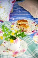 Mug of yellow wildflowers in front of floral plate of focaccia sandwiches on picnic blanket on bed