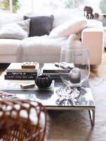 Candle in large glass vase and stacked books on low coffee table in front of white couch with scatter cushions