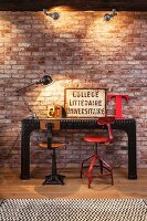Vintage swivel chairs in different colours and black metal table with studs against illuminated brick wall