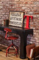 Red-painted, vintage swivel chair and ornaments on black, metal console table against brick wall