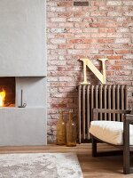 Partially visible armchair next to vintage radiator and open concrete fireplace set in brick wall