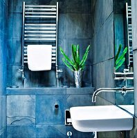 Modern bathroom with blue marbled wall tiles, sink with wall-mounted tap fittings and stainless steel towel warmer