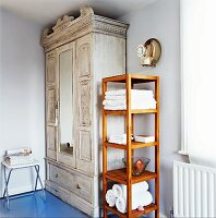 Plain wooden shelves next to white, shabby-chic vintage wardrobe in corner