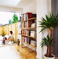 Bookshelves against wall in front of open terrace door with view of woman sitting on garden chair
