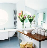 Washstand with counter-top basin next to vintage china containers and free-standing bathtub below porthole window