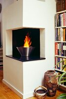 Antique floor vase in front of bookcase and fire burning in fire bowl in protruding fireplace