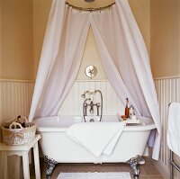 Free-standing, clawfoot bathtub with draped shower curtain in wood-panelled bathroom