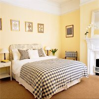 Elegant bedroom with yellow-painted walls and checked throw on double bed
