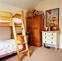 Country-house-style chest of drawers, collection of soft toys on wardrobe and nostalgic bedspreads on bunk beds