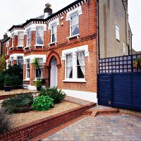 English semi-detached house with restored brick facade and planted gravel flower bed in front garden