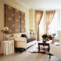 Triptych artwork above cream sofa and draped curtains in bay window of traditional interior