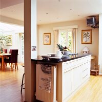 Kitchen island in elegant, country-house style; wall-mounted TV below ceiling