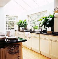 Elegant, white, country-house kitchen with black worksurface below glass ceiling and open louver blinds on windows