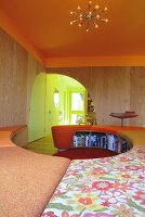 Curved bench with colourful seat cushions and orange-painted ceiling with sunburst pendant lamp; quarter-circular doorway in background