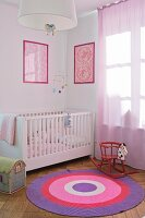 Nursery with framed, patterned pictures over white cot; rocking horse on round rug in shades of lilac and pink