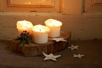 Lit candles and Christmas decorations on wooden board and floor