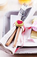 Cutlery and linen napkin in simple napkin ring lovingly decorated with gold bottle cap and heart motif