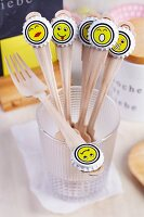 Wooden forks with whimsical smiley face stickers on bottle tops arranged decoratively for party buffet