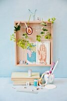 Lady's mantle flowers hung up to dry in wooden box with cards on wall above desk