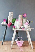 Utensils such as rolls of wallpaper, bottles and vases decorated with cosmos flowers on rustic stools against grey background