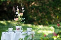 Romantic arrangement of roses in nostalgic teacup on garden table with white tablecloth and two teacups