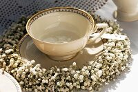 Nostalgic, gold-rimmed teacup festively decorated with wreath of gypsophila