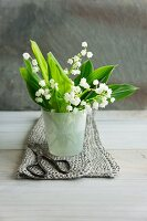 Lily of the valley posy in glass container and garden scissors