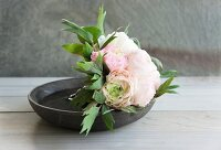 Peonies in dish on wooden surface