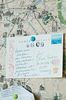 Printed and hand-written postcard on pin board with map as background