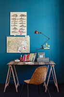 Desk with top covered in tartan fabric and wooden trestles, grey cardboard boxes, books, desk lamp and old map