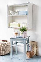 Upcycling - grey blue stool between pouffe and wooden mortar on floor below nostalgic crockery on shelf unit
