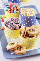 Polka-dot paper muffin cases of colourful biscuits, Smarties and puffed rice on tray