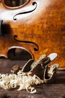 Wood shavings and violin-maker's plane in front of violin body