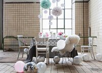Listed industrial interior used as party location with delicate, romantic furnishings and decorated with balloons and paper pompoms