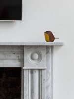 Small, minimalist wooden bird sitting on marble fire surround
