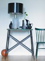 Table lamp with black lampshade next to collection of vases on rustic, metal console table