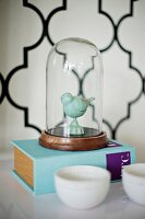 Bird figurine under glass cover on thick book; wallpaper with Oriental tile pattern in blurred background