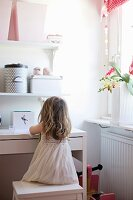 Little girl sitting on stool at white desk and storage boxes on floating shelves