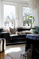 Black leather sofa with pale scatter cushions below window