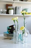 Yellow carnations in various glass bottles in front of stacked colourful crockery on table